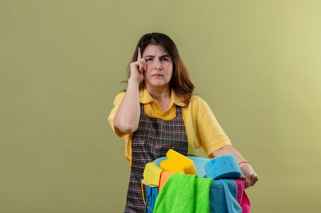 Kobieta w średnim wieku w fartuchu trzymająca wiadro z narzędziami do czyszczenia, wskazująca palcem w górę, przypominająca sobie, by nie zapomnieć o ważnej rzeczy