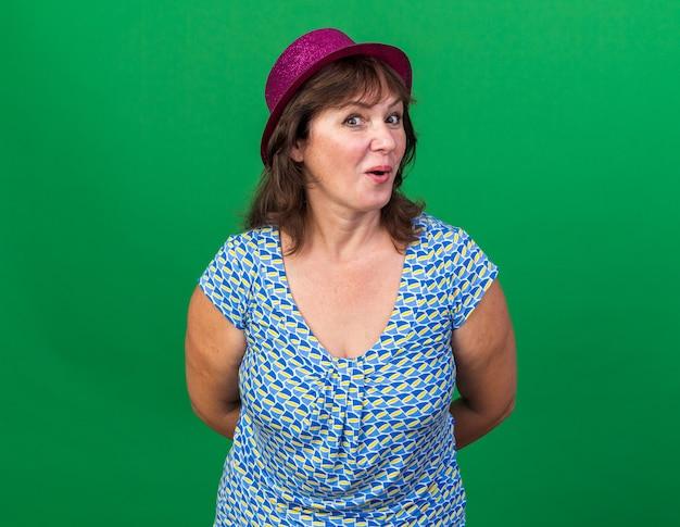 Kobieta w średnim wieku w imprezowej czapce szczęśliwa i zaskoczona świętująca przyjęcie urodzinowe stojąca nad zieloną ścianą