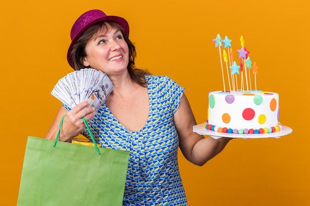 Kobieta w średnim wieku w imprezowej czapce trzymająca papierową torbę z prezentami trzymająca tort urodzinowy i gotówkę szczęśliwa i zadowolona uśmiechnięta radośnie świętująca przyjęcie urodzinowe stojąca nad pomarańczową ścianą