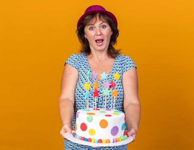 Kobieta w średnim wieku w imprezowej czapce trzymająca tort urodzinowy szczęśliwa i zaskoczona świętująca przyjęcie urodzinowe stojąca nad pomarańczową ścianą