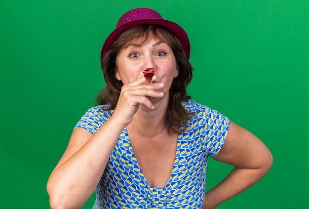Kobieta w średnim wieku w imprezowym kapeluszu dmuchająca w gwizdek szczęśliwa i wesoła