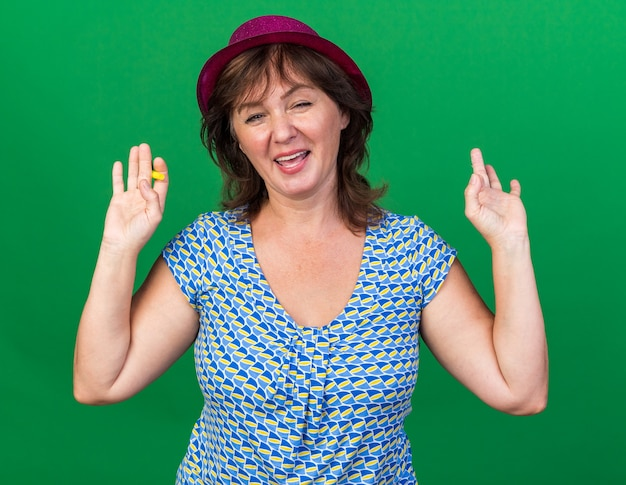 Kobieta w średnim wieku w imprezowym kapeluszu trzymająca gwizdek szczęśliwa i wesoła z uniesionymi ramionami świętująca przyjęcie urodzinowe stojące nad zieloną ścianą