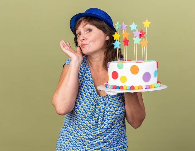 Kobieta w średnim wieku w imprezowym kapeluszu trzymająca tort urodzinowy odwracająca wzrok z nieśmiałym uśmiechem na twarzy świętująca przyjęcie urodzinowe stojące nad zieloną ścianą
