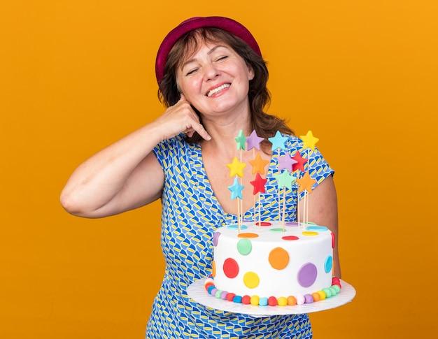 """Kobieta w średnim wieku w imprezowym kapeluszu trzymająca tort urodzinowy uśmiechnięta radośnie szczęśliwa i pozytywna wykonująca gest """"zadzwoń do mnie"""" świętująca przyjęcie urodzinowe stojąc nad pomarańczową ścianą"""