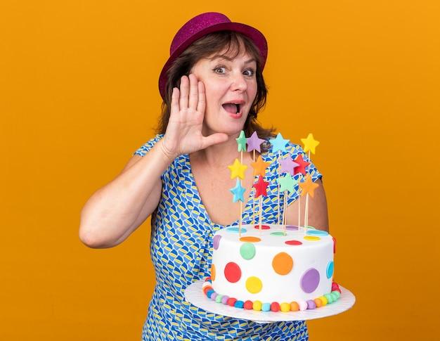 Kobieta w średnim wieku w imprezowym kapeluszu trzymająca tort urodzinowy z ręką nad uchem, próbująca usłyszeć plotki