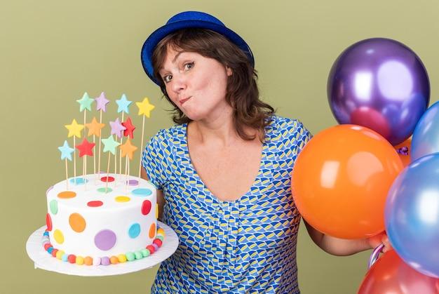 Kobieta w średnim wieku w imprezowym kapeluszu z pękiem kolorowych balonów trzymająca tort urodzinowy zdezorientowana