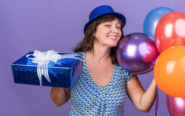 Kobieta w średnim wieku w imprezowym kapeluszu z wiązką kolorowych balonów trzymająca prezent, uśmiechnięta radośnie
