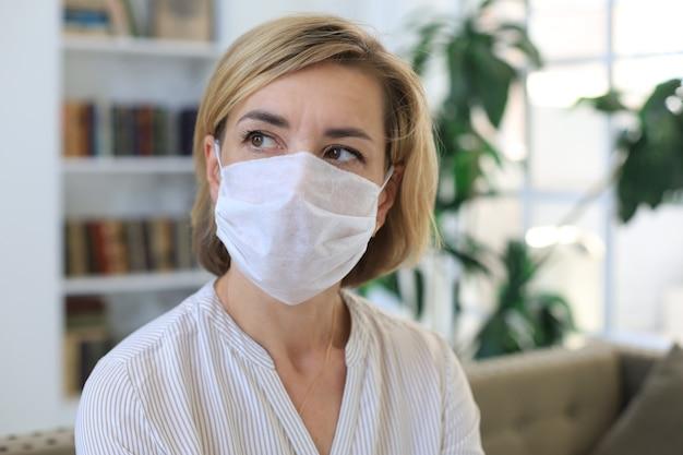 Kobieta w średnim wieku w masce medycznej w domu podczas sytuacji epidemicznej.
