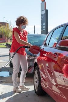 Kobieta w średnim wieku w masce ochronnej tankowała samochód na stacji benzynowej