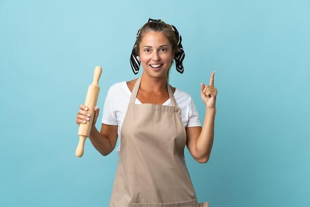 Kobieta w średnim wieku w mundurze szefa kuchni myśli pomysł wskazując palcem w górę
