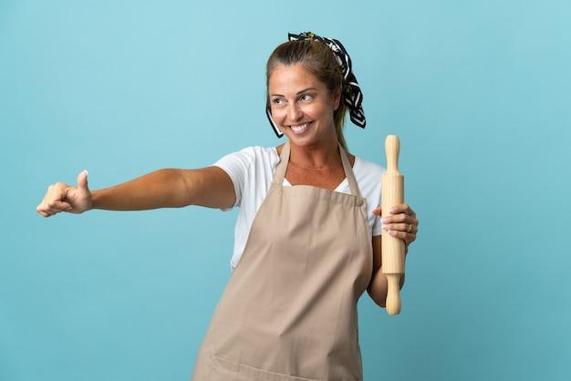 Kobieta w średnim wieku w mundurze szefa kuchni, podając kciuki do góry gest