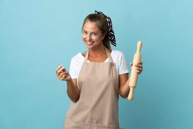 Kobieta w średnim wieku w mundurze szefa kuchni robi gest pieniędzy