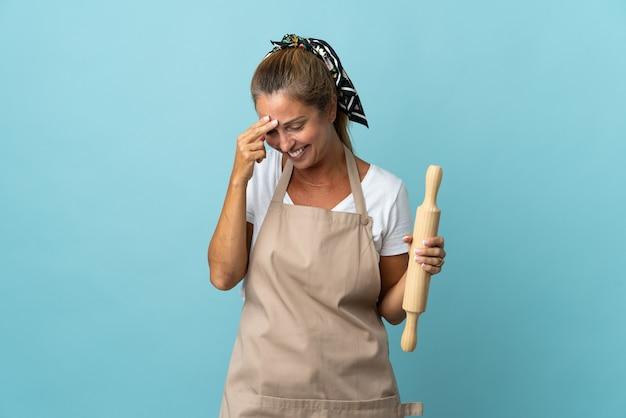 Kobieta w średnim wieku w mundurze szefa kuchni, śmiejąc się