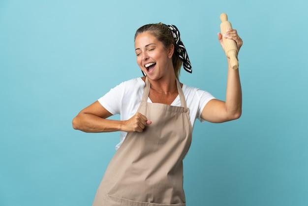 Kobieta w średnim wieku w mundurze szefa kuchni świętuje zwycięstwo