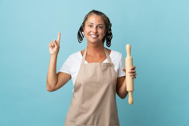 Kobieta w średnim wieku w mundurze szefa kuchni, wskazując na świetny pomysł