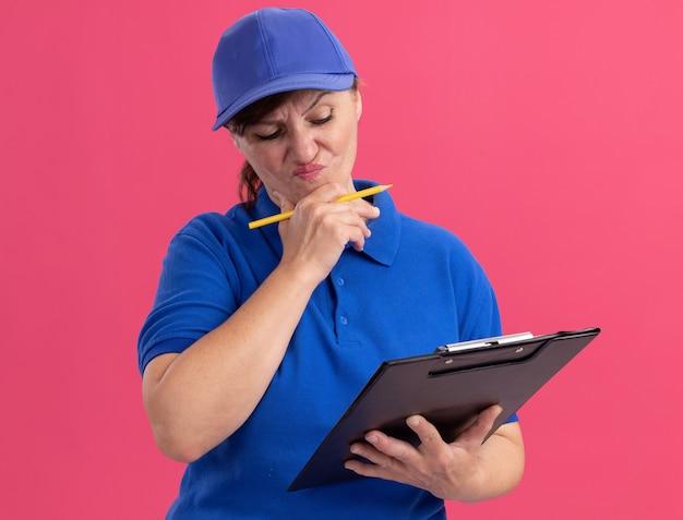 Kobieta w średnim wieku w niebieskim mundurze i czapce trzymająca schowek i ołówek wyglądająca na zdezorientowaną i bardzo niespokojną stojącą nad różową ścianą