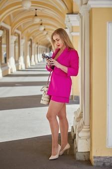 Kobieta w średnim wieku w różowym garniturze ze smartfonem w rękach stoi w łukowej galerii handlowej.