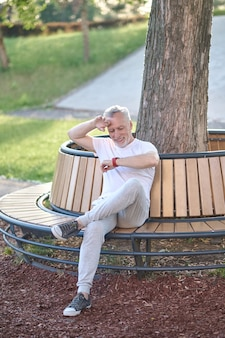 Kobieta w średnim wieku w stroju sportowym odpoczywa po treningu