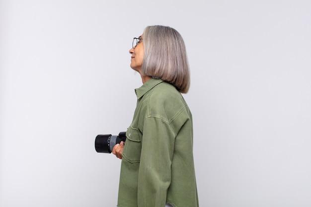 Kobieta w średnim wieku w widoku profilu, chcąca skopiować przestrzeń do przodu, myśląca, wyobrażająca sobie lub marząca. koncepcja fotografa
