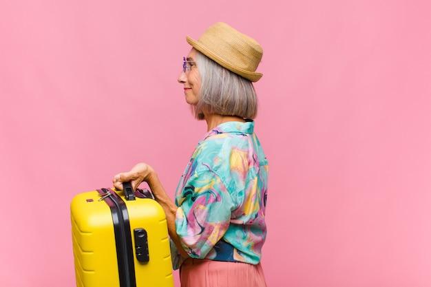 Kobieta w średnim wieku w widoku profilu, która chce skopiować przestrzeń do przodu, myśleć, wyobrażać sobie lub marzyć