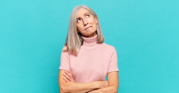 Kobieta w średnim wieku wątpi lub myśli, przygryza wargę i czuje się niepewnie i zdenerwowana, chcąc skopiować przestrzeń z boku