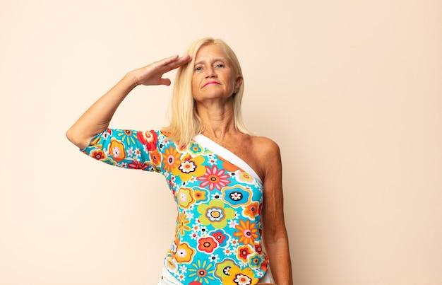 Kobieta w średnim wieku, witając aparat z wojskowym pozdrowieniem na białym tle