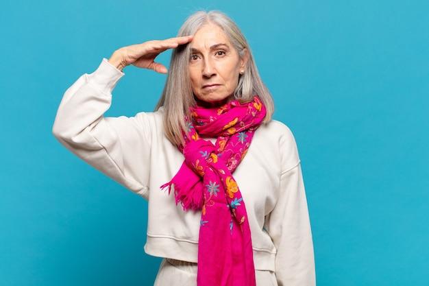 Kobieta w średnim wieku witająca kamerę salutem wojskowym w akcie honorowym i patriotycznym, okazująca szacunek