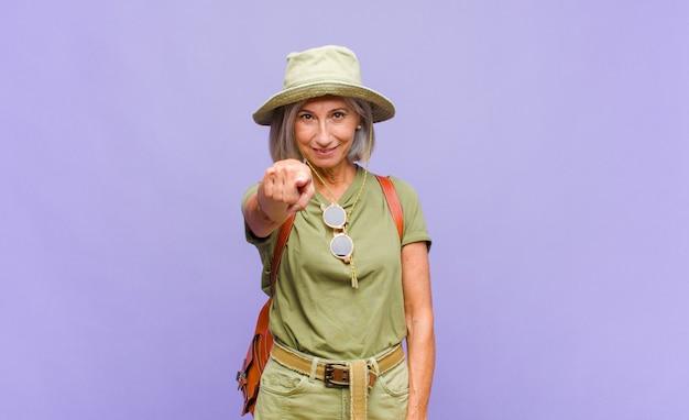 Kobieta w średnim wieku, wskazująca na aparat z zadowolonym, pewnym siebie, przyjaznym uśmiechem, wybiera ciebie