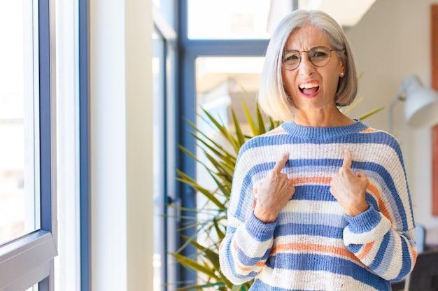 Kobieta w średnim wieku wskazująca na siebie z zagubionym i pytającym spojrzeniem, zszokowana i zaskoczona wyborem