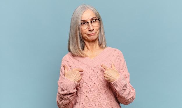 Kobieta w średnim wieku wskazująca na siebie z zakłopotanym i zagadkowym spojrzeniem, zszokowana i zaskoczona wyborem