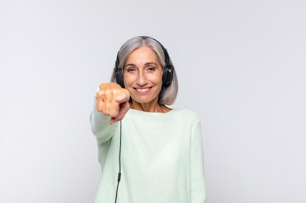 Kobieta w średnim wieku wskazująca z zadowolonym, pewnym siebie, przyjaznym uśmiechem, wybiera ciebie. koncepcja muzyki