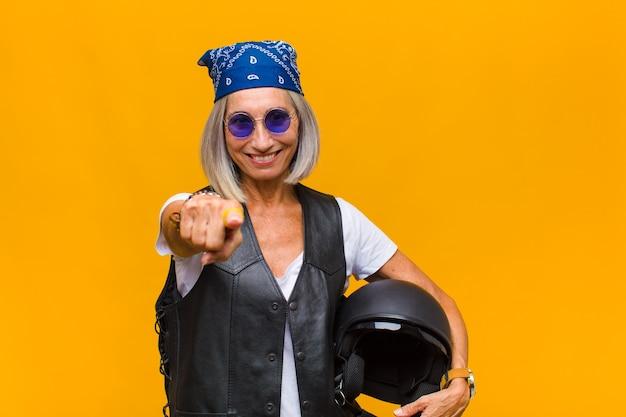 Kobieta w średnim wieku wskazująca z zadowolonym, pewnym siebie, przyjaznym uśmiechem, wybiera ciebie