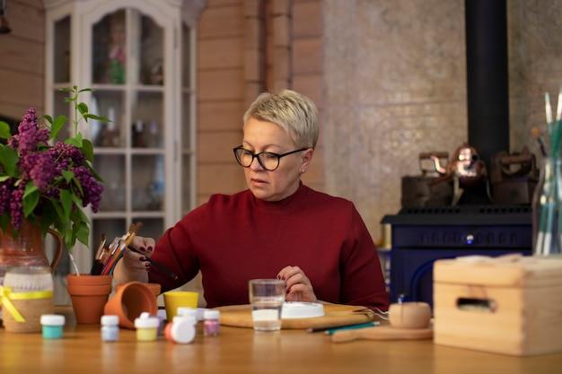 Kobieta w średnim wieku wybiera ołówek do rysowania w przytulnym wiejskim domu z kominkiem