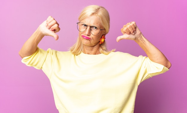 Kobieta w średnim wieku wygląda na smutną, rozczarowaną lub złą, pokazując kciuk w dół w niezgodzie, czując się sfrustrowana