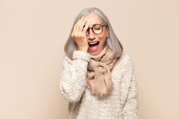 Kobieta w średnim wieku wygląda na zaspaną, znudzoną i ziewającą, z bólem głowy i jedną ręką zakrywającą połowę twarzy
