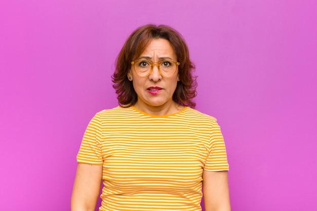 Kobieta w średnim wieku wygląda zdziwiona i zdezorientowana, przygryzając wargę nerwowym gestem, nie znając odpowiedzi na problem z fioletową ścianą