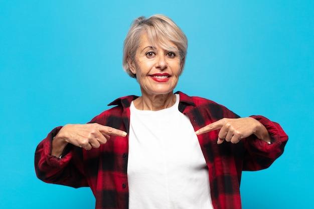 Kobieta w średnim wieku wyglądająca dumnie, pozytywnie i swobodnie, wskazująca obiema rękami na klatkę piersiową