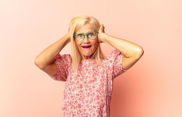Kobieta w średnim wieku wyglądająca jak szczęśliwa, dumna i usatysfakcjonowana osoba, która uśmiecha się ze skrzyżowanymi rękami
