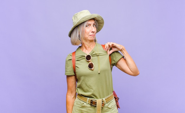 Kobieta w średnim wieku wyglądająca na arogancką, odnoszącą sukcesy, pozytywną i dumną, wskazującą na siebie