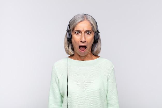 Kobieta w średnim wieku wyglądająca na bardzo zszokowaną lub zaskoczoną, patrząc z otwartymi ustami i mówiącą wow. koncepcja muzyki
