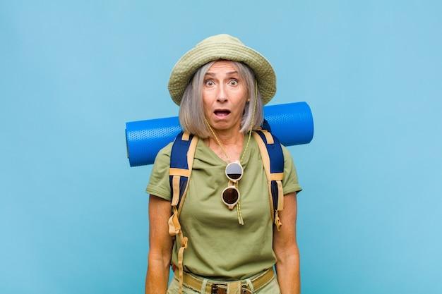 Kobieta w średnim wieku wyglądająca na bardzo zszokowaną lub zaskoczoną, patrząc z otwartymi ustami i mówiącą wow