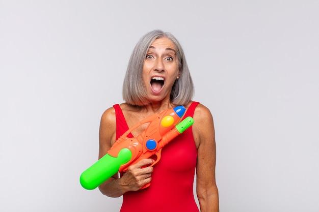 Kobieta w średnim wieku wyglądająca na bardzo zszokowaną lub zaskoczoną