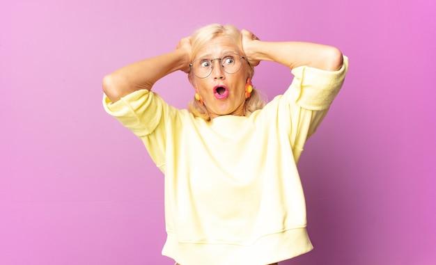 Kobieta w średnim wieku wyglądająca na podekscytowaną i zaskoczoną, z otwartymi ustami i obiema rękami na głowie, czując się jak szczęśliwy zwycięzca