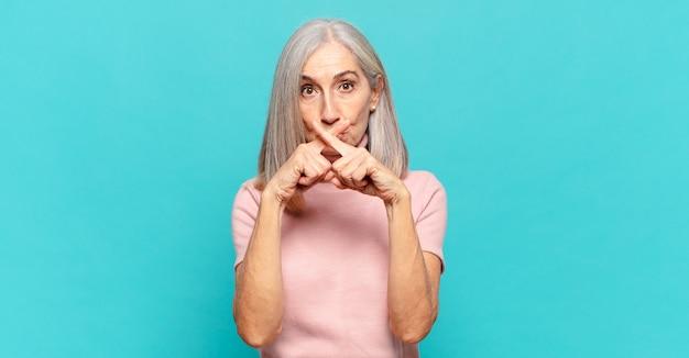 Kobieta w średnim wieku wyglądająca na poważną i niezadowoloną, z dwoma palcami skrzyżowanymi z przodu, prosząc o ciszę