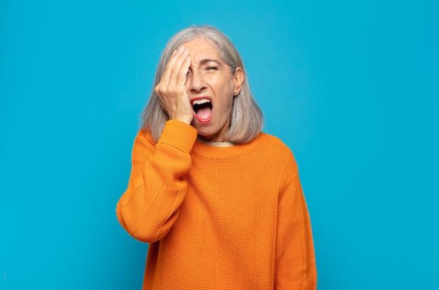 Kobieta w średnim wieku wyglądająca na senną, znudzoną i ziewającą, z bólem głowy i jedną ręką zakrywającą połowę twarzy