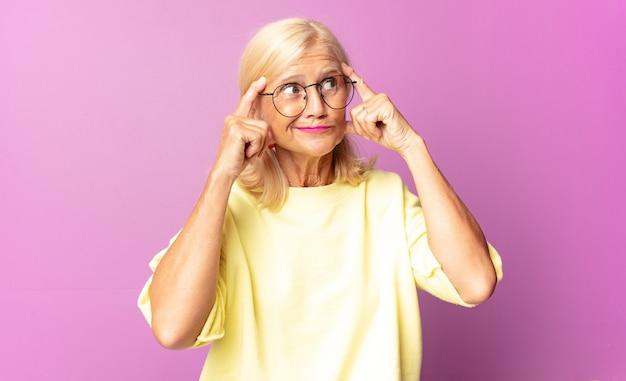Kobieta w średnim wieku wyglądająca na skoncentrowaną i intensywnie myślącą nad pomysłem