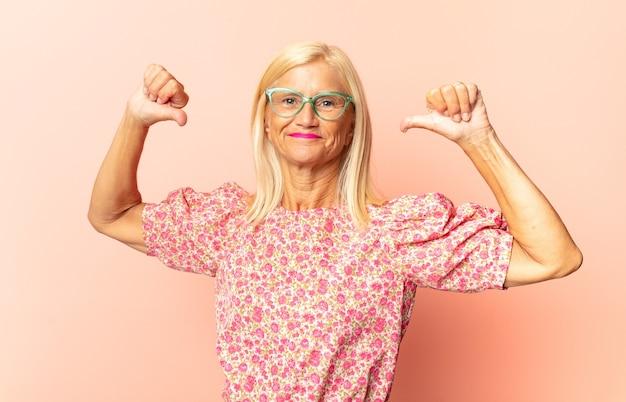 Kobieta w średnim wieku wyglądająca na smutną, rozczarowaną lub zła, pokazująca kciuki w dół w wyrazie sprzeciwu