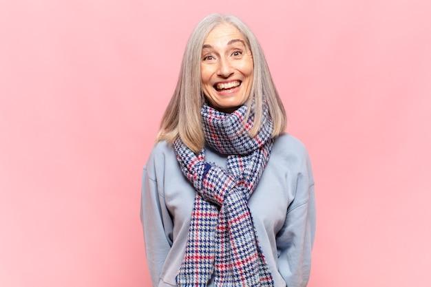 Kobieta w średnim wieku wyglądająca na szczęśliwą i przyjemnie zaskoczoną, podekscytowana zafascynowaną i zszokowaną miną