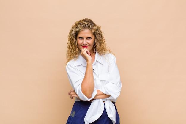 Kobieta w średnim wieku wyglądająca na szczęśliwą i uśmiechniętą z ręką na brodzie, zastanawiająca się lub zadająca pytanie, porównująca opcje