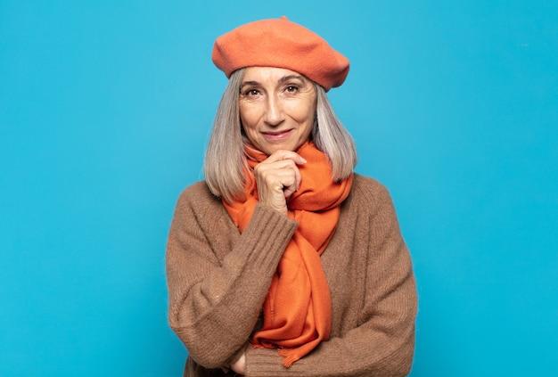 Kobieta w średnim wieku wyglądająca na szczęśliwą i uśmiechniętą z ręką na brodzie, zastanawiająca się lub zadająca pytanie